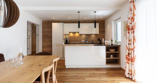 Voll ausgestattete Küche mit angrenzenden Esstisch aus hellem Holz für bis zu 6 Personen