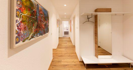 Vorzimmer mit großer Garderobe und Spiegel für genügend Platz zum Verstauen von Jacken und Schuhe