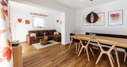 Esstisch für 6 Personen aus hellem Holz im naturbezogenen Ambiete und angrenzendes Wohnzimmer