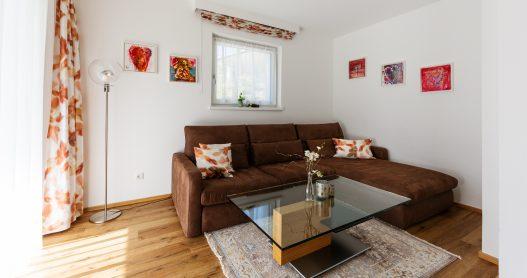 Wohnzimmer mit Couch, Tisch, Flatscreen TV, moderner Hifi-Anlage und direkter Zugang zum Garten