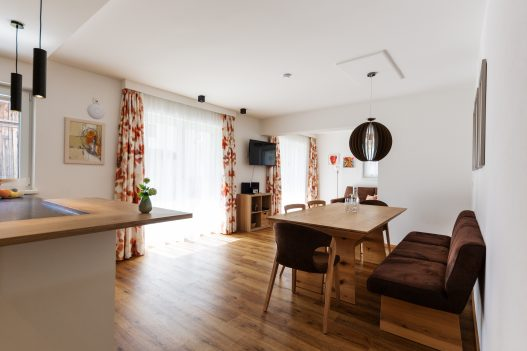 Wohnküche im naturbezogenen Ambiente mit Esstisch für bis zu 6 Personen und Zugang zum Garten