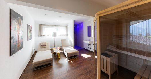 Wellness- und Ruheraum mit finnischer Sauna, Dusche und Aromadiffuser in entspannten blaulicht Ambiente