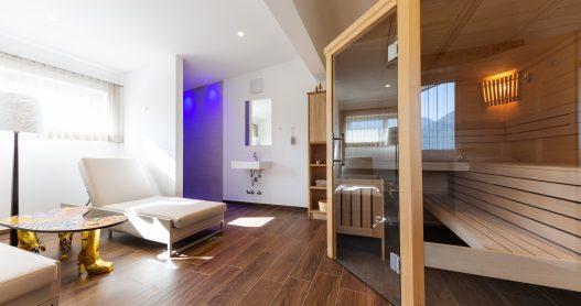 Wellness Ruheraum mit finnischer Sauna, Dusche und Aromadiffuser in entspannten blaulicht Ambiente