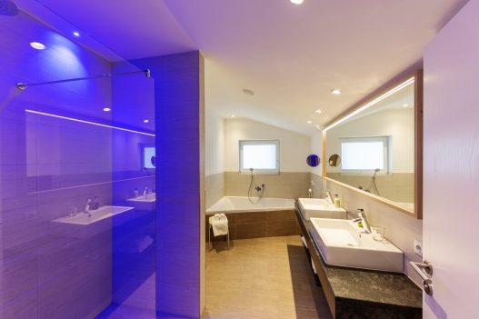 Badezimmer mit großer Badewanne, 2 Waschbecken, einer Toilette und eine mit Glas abgetrennte Dusche