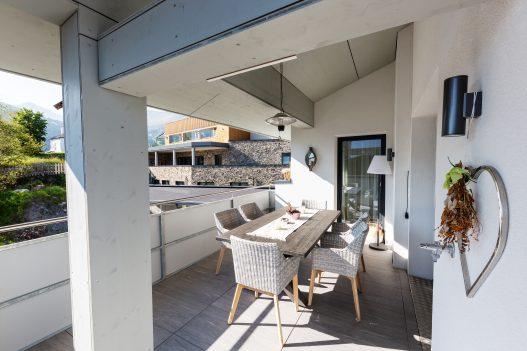 Großzügige und überdachte Terrasse mit Sitzgruppe und Tisch für 4 Personen und Zugang zur Wohnküche