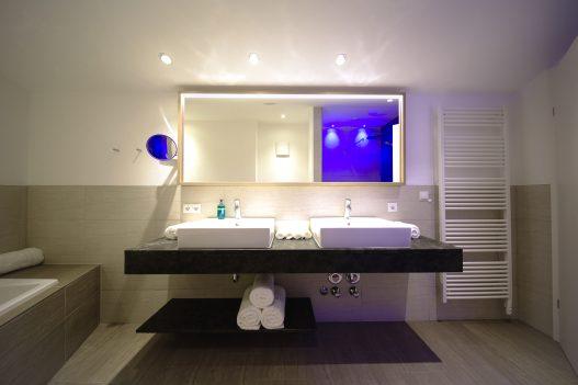 Zwei großzügige Waschbecken, großem Spiegel und Handtuchtrockner für Handtücher und Bademäntel