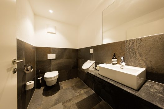 Separates WC mit Sitztoilette und Pissoir. Toilettenpapier, Handseife und Creme wird bereitgestellt