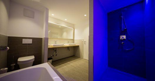 Badezimmer mit 2 Waschbecken, abgetrennte Dusche, Toilette, Badewanne und Fenster für Tageslicht