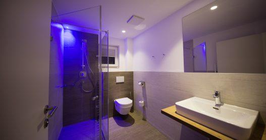 Zweites Badezimmer mit Waschbecken, Dusche, Toilette, Handtuchtrockner und Fenster für Tageslicht