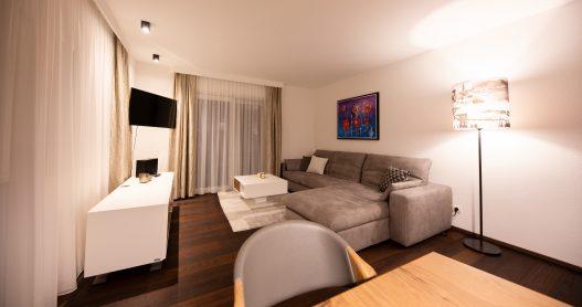Großes Wohnzimmer mit Couch, Tisch, Flatscreen TV, moderner Hifi-Anlage und Zugang zur Terrasse