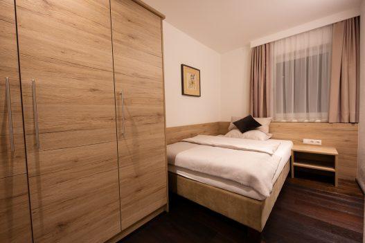 Schlafzimmer mit großzügigen Queensize-Bett mit Allergikerbettwäsche und Einbauschrank sowie Fenster