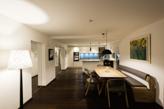 Wohnküche mit Esstisch für bis zu 6 Personen aus hellem, lokalem Holz im naturbezogenen Ambiente