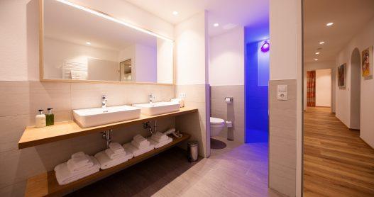 Großes Badezimmer mit 2 Waschbecken, abgetrennter Dusche und Toilette in entspannten blauen Licht