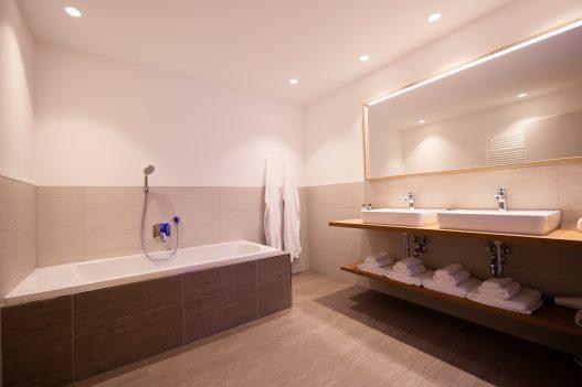Badezimmer mit großer Badewanne, 2 Waschbecken, Handtuchtrockner, Shampoo, Duschgel und Seife